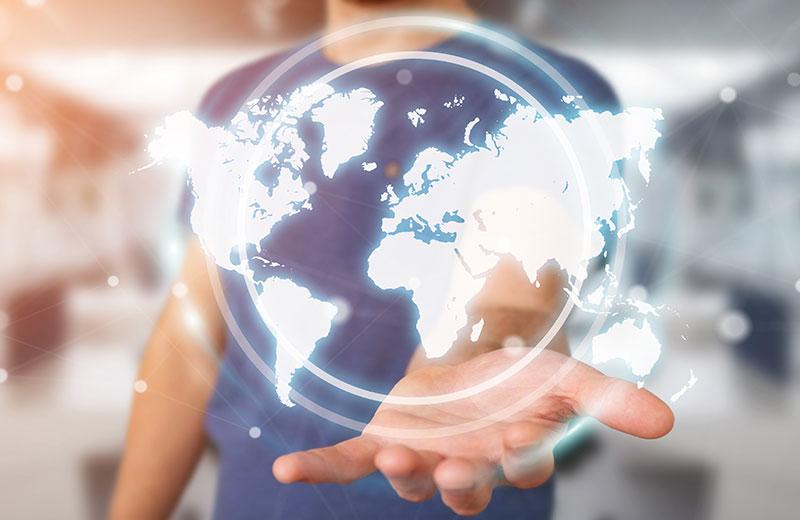 Eine Person hält das holografische Abbild der Erdkugel auf seiner Hand.